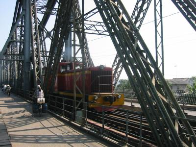 Photo of bridge with bicycles and train